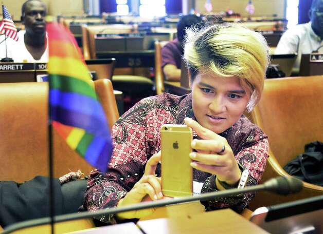 LGBT activist Julia Ginting from Indonesia photographs a rainbow flag in the Assembly Chamber during their visit to Albany and the State Capitol Friday August 14, 2015 in Albany, NY.  (John Carl D'Annibale / Times Union) Photo: John Carl D'Annibale / 00033014A