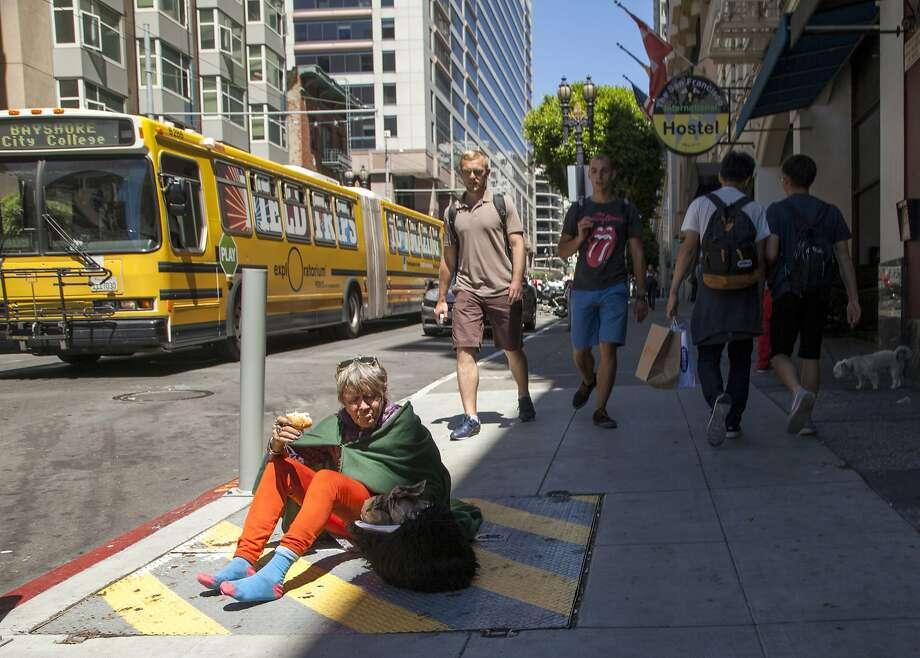 A woman sits along Mason Street in San Francisco, which bars sitting or lying on sidewalks between 7 a.m. and 11 p.m. Photo: Santiago Mejia, Special To The Chronicle