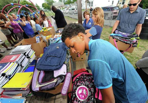 Volunteers from the Schenectady Inner City Ministry, Schenectady Youth basketball and Schenectady Police Department hand out backpacks and school supplies at  Jerry Burrell Park on Friday Aug. 14, 2015 in Schenectady, N.Y.  (Michael P. Farrell/Times Union) Photo: Michael P. Farrell / 00033009A