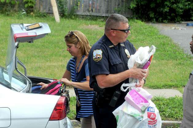 Summer lunch director Rachel Curtis, left, and Police Chief Brian A. Kilcullen unload donated school supplies as volunteers from the Schenectady Inner City Ministry, Schenectady Youth basketball and Schenectady Police Department hand out backpacks and school supplies at  Jerry Burrell Park on Friday Aug. 14, 2015 in Schenectady, N.Y.  (Michael P. Farrell/Times Union) Photo: Michael P. Farrell / 00033009A