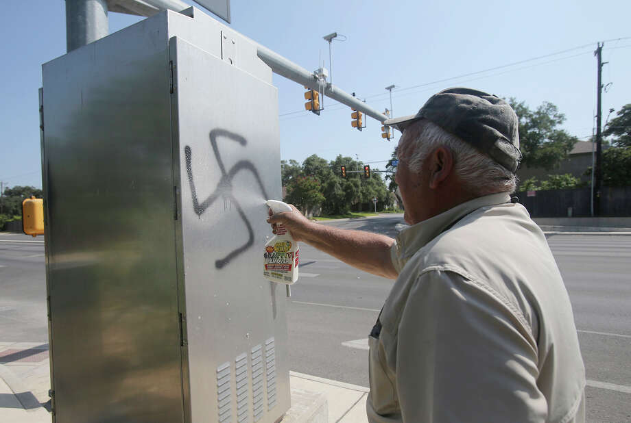 Sam Ferris washes away a swastika at Sholom Drive and Northwest Military Highway in San Antonio, that was spray painted on an electrical box. San Antonio police are investigating anti-Semitic graffiti that was found spray-painted on about 30 buildings and vehicles. Photo: John Davenport /Associated Press / San Antonio Express-News