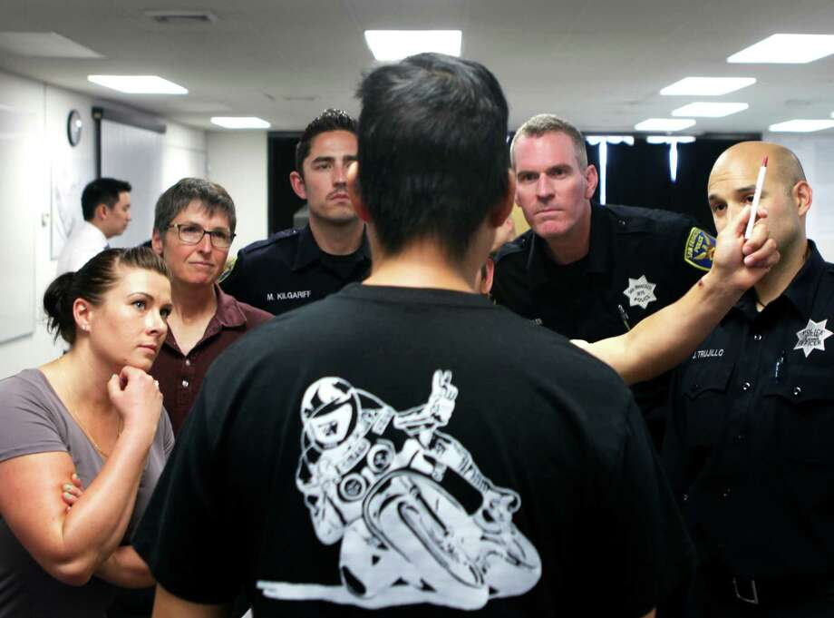 Officers watch as a horizontal gaze test is conducted on Kevin Lee, who voluntarily got intoxicated as part of the S.F. Police Department's wet lab class to teach officers to recognize when a person they are questioning is drunk. Photo: Cameron Robert / Cameron Robert / The Chronicle / ONLINE_YES