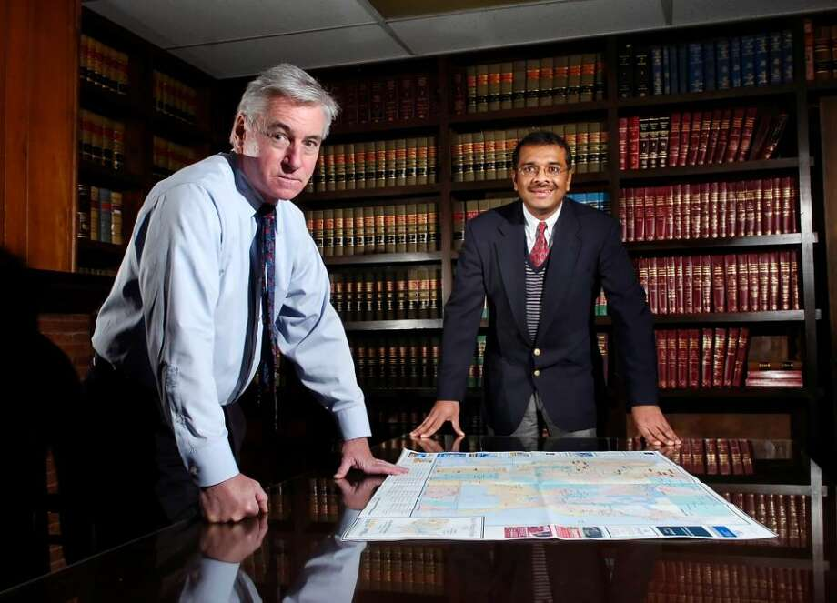 "John Evans, a Manager of Business Development for Krishnan & Associates, left, and the Principal of Krishnan Associates, Ravi Krishnan, pose in the conference room of Krishnan Associates in Stamford.  The firm specializes in ""Innovative Solutions for the Power Industry"", according to Ravi Krishnan. Photo: Bob Luckey / Stamford Advocate"