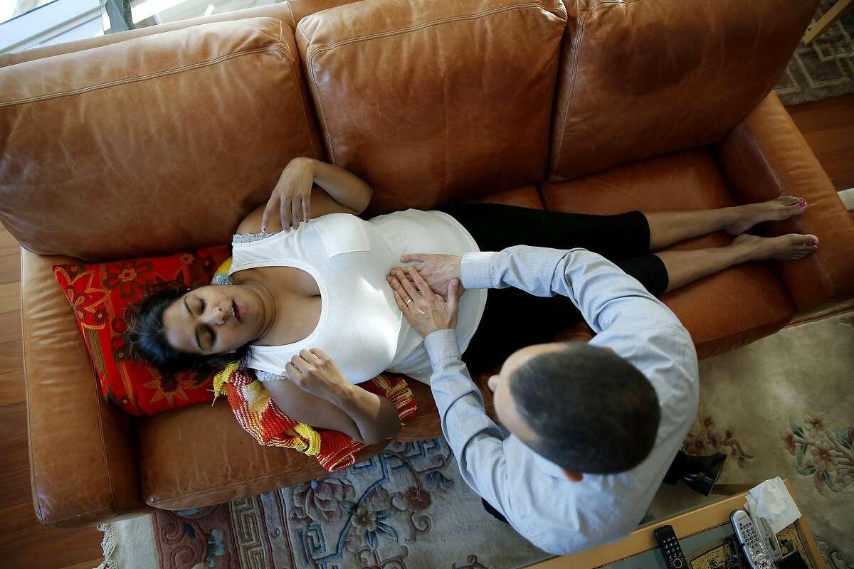 Dr. Matt Walvick examines Shima Lal's abdomen during a house call in San Francisco, California, on Thursday, Aug. 13, 2015.