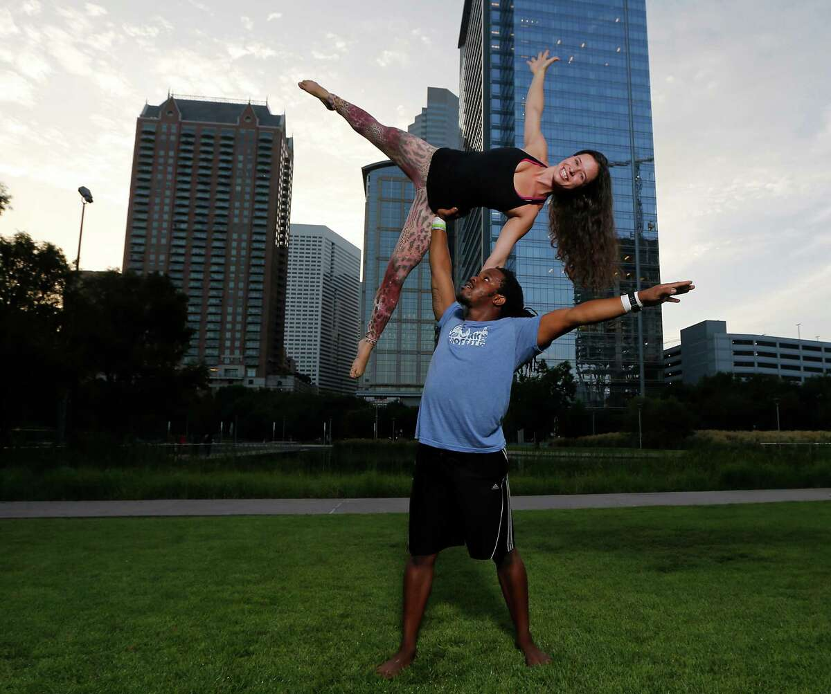 Acroyoga instructors Nosa bottom, and his wife Susie Edebor show the high-side star pose.