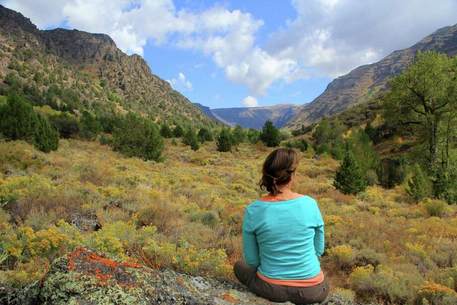A woman takes in a gorgeous mountain view at Big Indian Gorge by Steens Mountain in Oregon. Photo: Zach Urness /Associated Press / Statesman-Journal