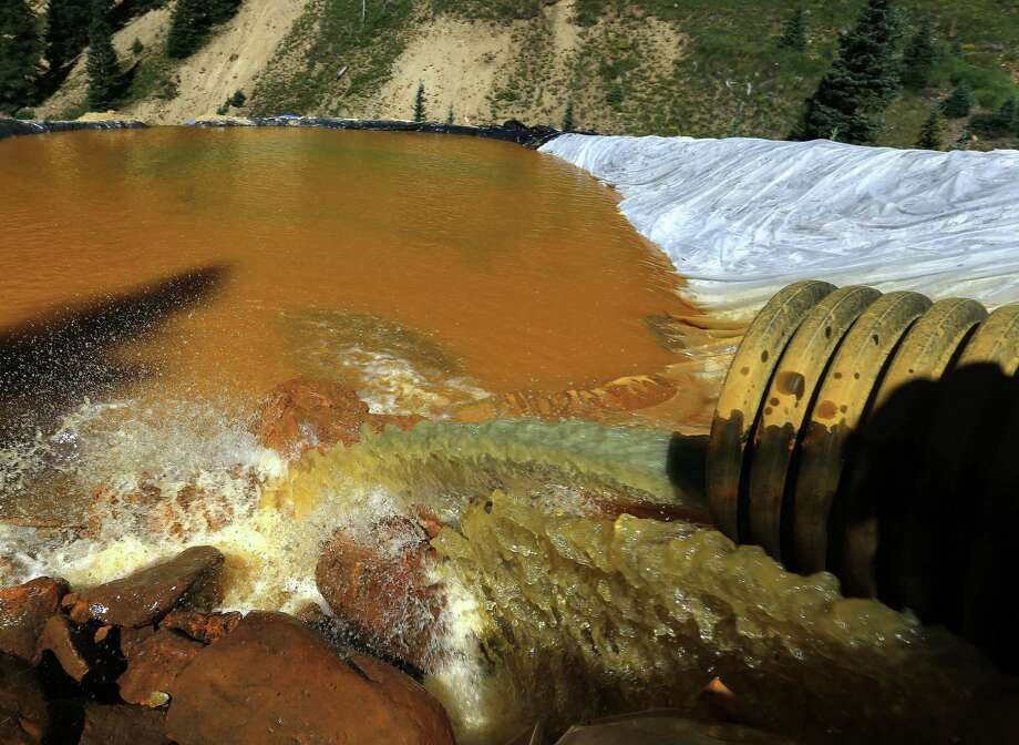 Water flows through a series of sediment retention ponds built to reduce heavy metal and chemical contaminants from the Gold King Mine wastewater accident, in the spillway about 1/4 mile downstream from the mine, outside Silverton, Colo., Friday, Aug. 14, 2015. Officials have said that federal contractors accidentally released more than 3 million gallons of wastewater laden with heavy metals last week at the Gold King Mine near Silverton. The pollution flowed downstream to New Mexico and Utah. (AP Photo/Brennan Linsley) Photo: Brennan Linsley, STF / AP