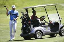 NBA basketball player Stephen Curry, left, returns a club to the cart as President Barack Obama, right, prepares to drive while golfing Friday, Aug. 14, 2015, at Farm Neck Golf Club, in Oak Bluffs, Mass., on the island of Martha's Vineyard. The president, first lady Michelle Obama, and daughter Sasha are vacationing on the island. (AP Photo/Steven Senne)