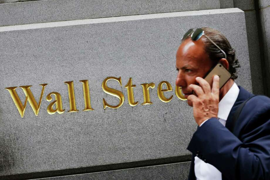FILE - In this Monday, July 6, 2015, file photo, a man uses a mobile phone while walking by a building in the Financial District in New York. Slightly disappointing European growth figures, notably out of France and Italy, weighed on stock markets Friday, Aug. 14, 2015, while oil prices sank to their lowest level since early 2009. (AP Photo/Mark Lennihan, File) ORG XMIT: NYSB502 Photo: Mark Lennihan / AP