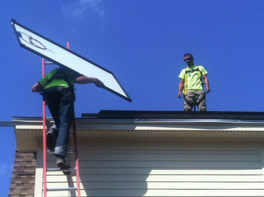 Monolith Solar technicians install solar panels on the roof of a home on Everett Avenue in Troy on Friday Aug. 14, 2015. (Larry Rulison / Times Union)