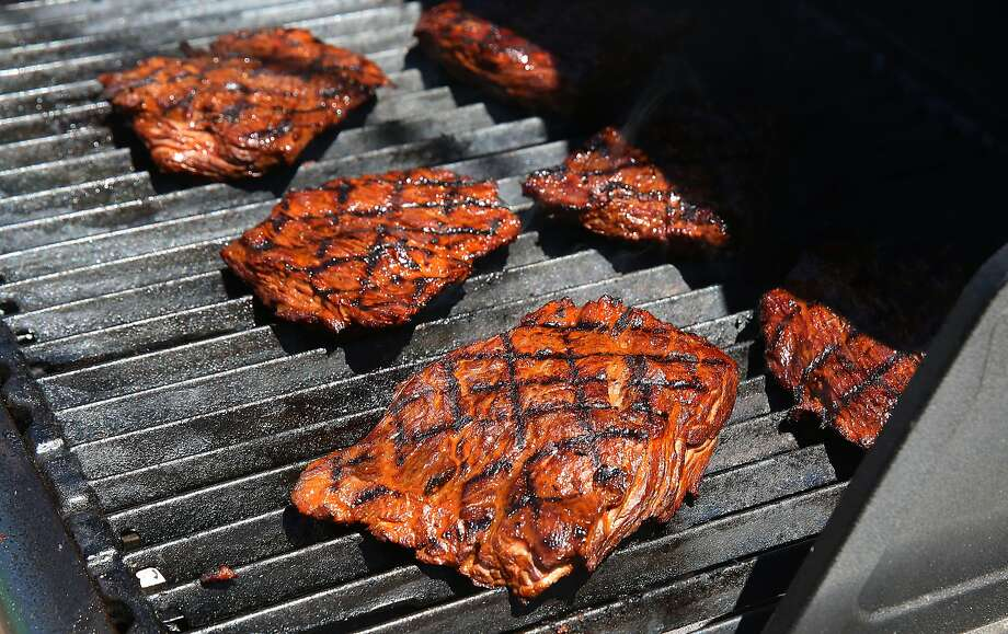 To meat lovers, barbecued cuts sizzling on the grill smell delicious. But could they increase your cancer risk? Photo: Liz Hafalia, The Chronicle