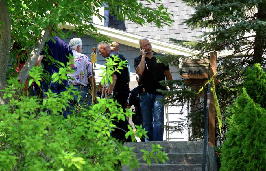 Shelton detectives along with members of the State police Major Crime Squad investigate at the scene of an untimely death at a home on Howe Avenue in Shelton, Conn., on Friday Aug. 14, 2015. Shelton police were called to the home at approximately 6:45 a.m. Upon arrival, the officers located a male victim deceased on the second floor of the residence. Photo: Christian Abraham / Hearst Connecticut Media / Connecticut Post