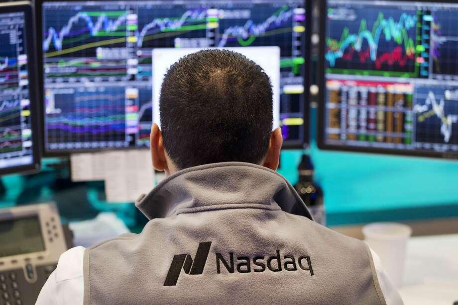 In this 2015 file photo, a Nasdaq employee monitors prices at the Nasdaq MarketSite, in New York.  Photo: Mark Lennihan, Associated Press