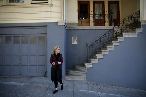 Theresa Flandrich, 60, shivers outside in her house in the North Beach neighborhood of San Francisco, California, on Friday, Aug. 14, 2015. She has lived in this house for 32 years and is now facing eviction.