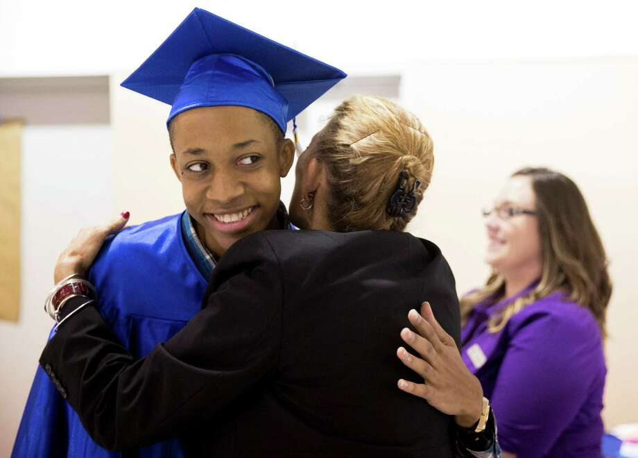 Graduate Nick Davison of Houston gets a hug from Judith Bell, interim president and CEO of Providence Place. Photo: Ray Whitehouse /San Antonio Express-News / 2015 San Antonio Express-News