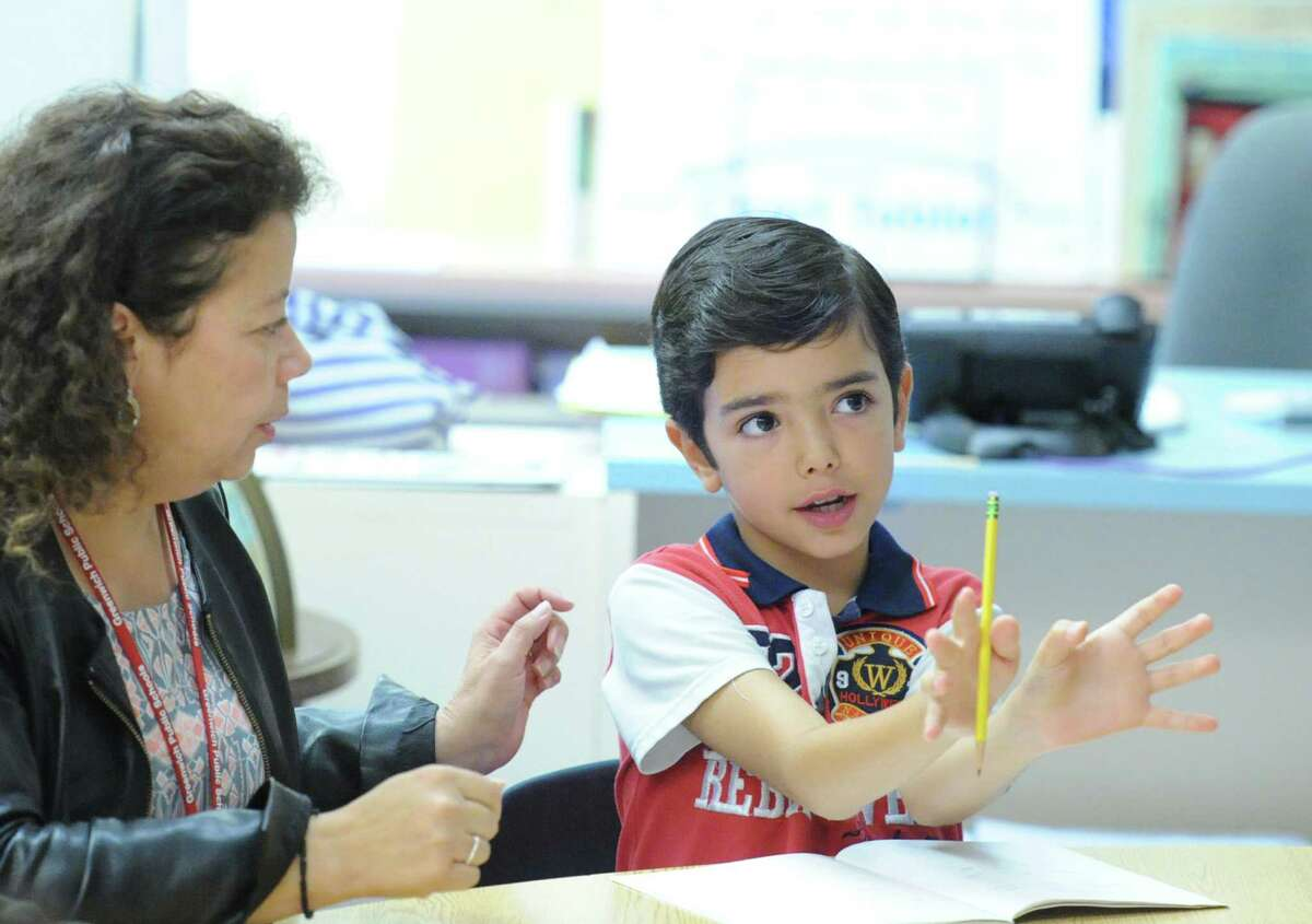 With help from Mabel Soto, left, an English as a Second Language class instructor, Alvaro Vivas, right, a native of Spain, answers a question during the ESL class for rising fourth-grade students at the Cos Cob School in Greewich, Conn., Tuesday, Aug. 11, 2015.