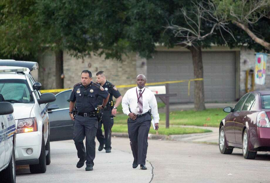 Authorities investigate the scene of a home invasion by two masked intruders on Friday in the 7200 block of Dew Mist in which two male occupants were shot. One of the men later died.  Photo: Cody Duty, Staff / © 2015 Houston Chronicle