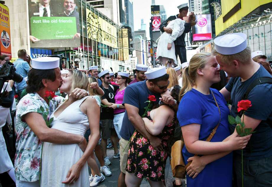 "Married couple Kenji and Kristen Kawasaki, far left, join others as they re-enact the iconic 1945 Alfred Eisenstaedt kiss photo, Friday, Aug. 14, 2015, in New York's Times Square. Dozens of couples gathered to re-enact the famous kiss that celebrated the end of World War II. A 25-foot high sculpture replica of the original kiss, top rear right, entitled ""Embracing Peace"" is in Times Square until Sunday. (AP Photo/Bebeto Matthews) ORG XMIT: NYBM101 Photo: Bebeto Matthews / AP"