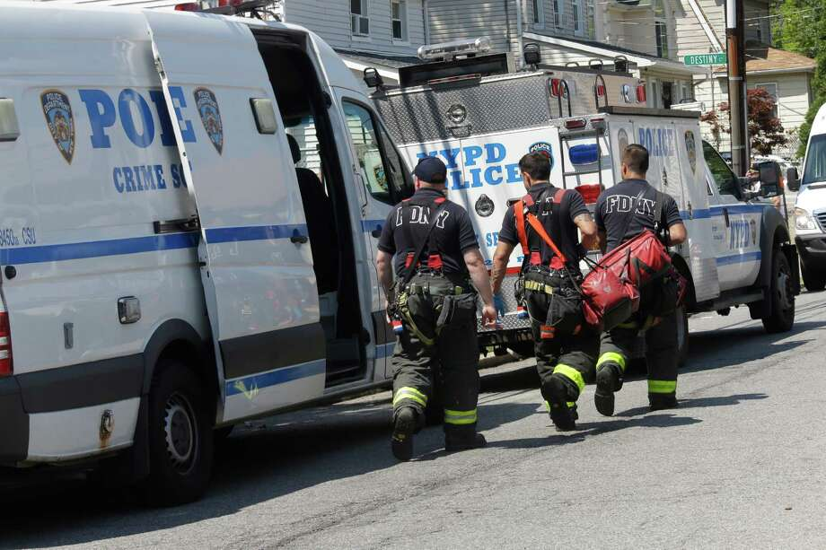 New York City firefighters carry their gear near the scene of a standoff, Friday, Aug. 14, 2015, in the Staten Island borough of New York. Garland Tyree, a high-ranking member of the Bloods street gang who was to be arrested on parole violations when he shot a firefighter responding to a call of smoke coming from his girlfriend's home, died Friday in a gunfight with police after a six-hour standoff, two police officials said.  (AP Photo/Mary Altaffer) ORG XMIT: NYMA108 Photo: Mary Altaffer / AP