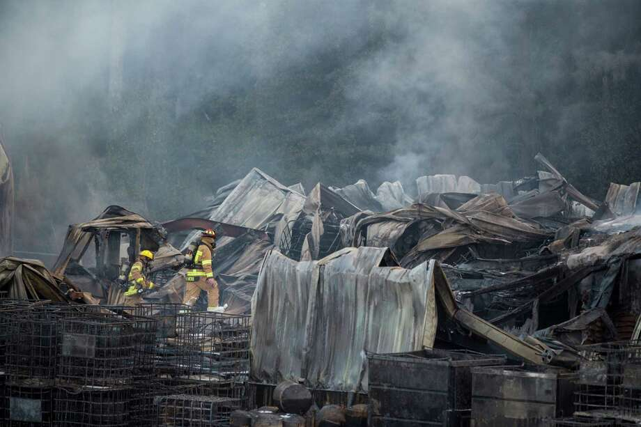 Firefighters walk through the smoldering remains of a warehouse Friday after the explosion at DrillChem Drilling Solutions, a company that lists its products as sealants and lubricants. Photo: Brett Coomer, Staff / © 2015 Houston Chronicle