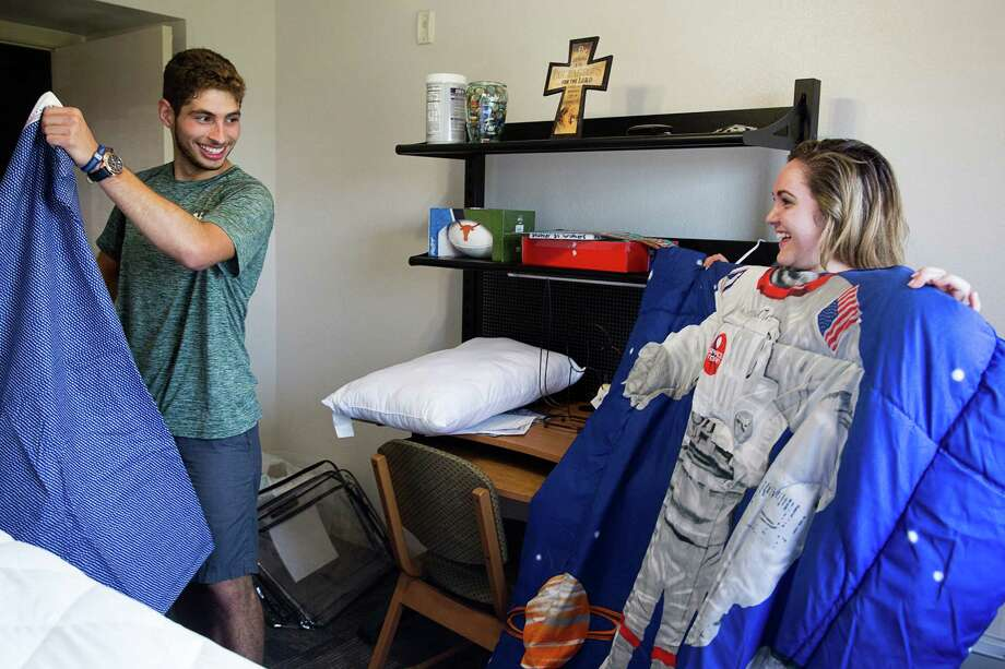 """ABOVE: Troy Lozano, an incoming freshman at UTSA in San Antonio, Texas, gets help moving into Chaparral Village residence hall from his friend Danielle DeCotis, whom he has known since kindergarten. Though Lozano, who attended Central Catholic High School, and DeCotis, who attended Antonian College Preparatory High School, went to rival high schools, they've remained friends. Lozano said his parents had to work so they could not help him move in so DeCotis volunteered to help. """"This morning was really filled with emotion,"""" Lozano said. """"[My parents] have raised me well for 18 years and now its time to see what I can do my own."""" Photo: Photos By Ray Whitehouse / San Antonio Express-News"""