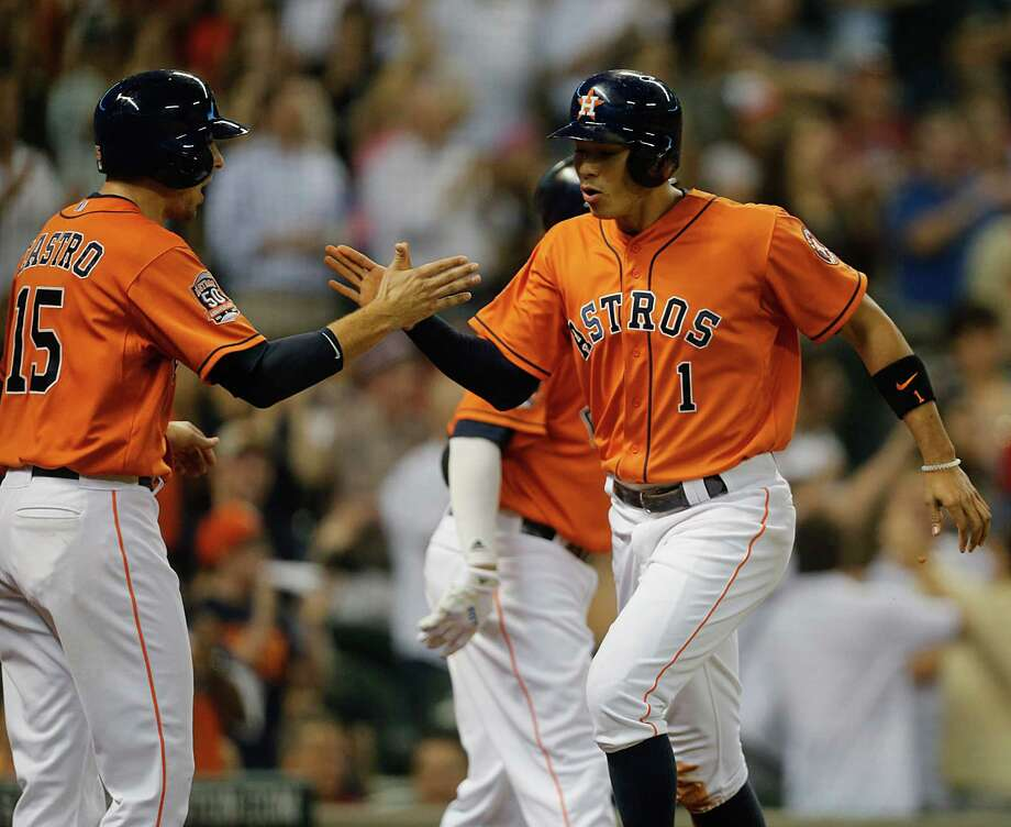 Jason Castro, left, and Carlos Correa rejoice at home plate when Correa scores during the Astros' pivotal three-run fifth inning at Minute Maid Park. Photo: James Nielsen, Staff / © 2015  Houston Chronicle