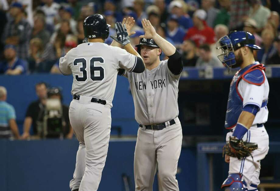 TORONTO, CANADA - AUGUST 14: Carlos Beltran #36 of the New York Yankees is congratulated by Brian McCann #34 after hitting a pinch-hit three-run home run in the eighth inning during MLB game action against the Toronto Blue Jays on August 14, 2015 at Rogers Centre in Toronto, Ontario, Canada. (Photo by Tom Szczerbowski/Getty Images) ORG XMIT: 538589755 Photo: Tom Szczerbowski / 2015 Getty Images