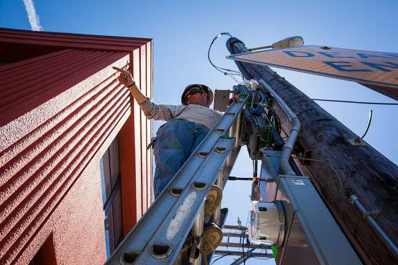 Brent Palmer, a contractor with Verizon Wireless, asks one of his crew members for a tool while he installs a remote radio unit (RRU) on a telephone pole in San Francisco, California, on Friday, Aug. 14, 2015. The RRU is a part of the cellular site that transmits the signal to the antenna.