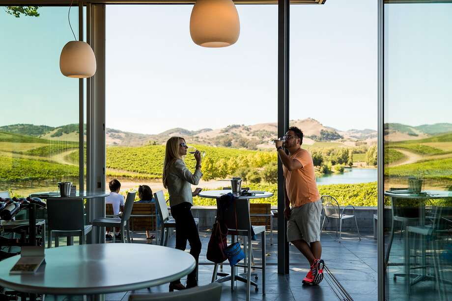Nicole Lyssy-Moore (center) sips wine in the Cuvaison Estate Wines tasting room, which overlooks the vineyard. Photo: Jason Henry, Special To The Chronicle