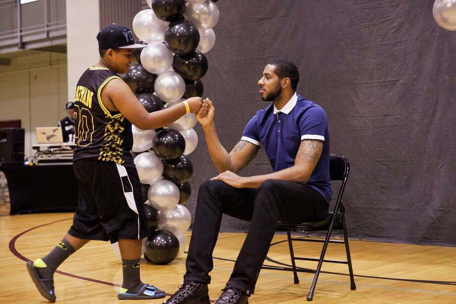 Spurs forward LaMarcus Aldridge fist-bumps Tony Aguirre, 12, during this year's back-to-school bash, hosted by LaMarcus Aldridge and H-E-B held for 200 students from 3rd Ð 5th grades and their families on Sat. Aug. 15, 2015 at the George Gervin Academy. Students received a backpack filled with a yearÕs worth of school supplies. / Julysa Sosa For the San Antonio Express-News