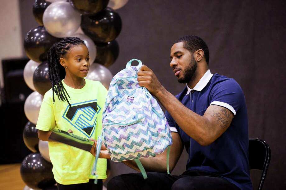 Spurs forward LaMarcus Aldridge hands Anaiya Trussell, 10, a backpack during this year's back-to-school bash, hosted by LaMarcus Aldridge and H-E-B held for 200 students from 3rd Ð 5th grades and their families on Sat. Aug. 15, 2015 at the George Gervin Academy. Students received a backpack filled with a yearÕs worth of school supplies. / Julysa Sosa For the San Antonio Express-News