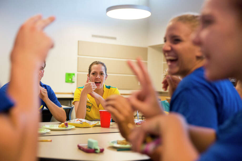 Members of the American and Australian deaf swim teams, including Hannah Britton (center) compare sign languages while visiting Friday at Sunshine Cottage School for Deaf Children on Hildebrand Avenue. Photo: Photos By Carolyn Van Houten /San Antonio Express-News / 2015 San Antonio Express-News