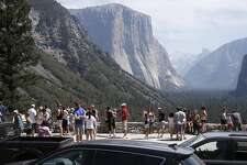 Cars and visitors fill the Tunnel View lookout, in Yosemite National Park, Calif., on Sat. August 15,  2015.
