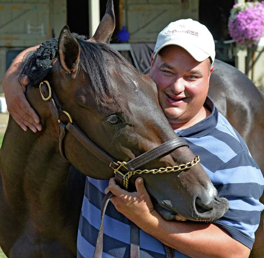 Trainer David Cannizzo gives Lil Schmo a hug Thursday morning Aug. 13, 2015 at the Saratoga Race Course in Saratoga Springs, N.Y.     (Skip Dickstein/Times Union) Photo: SKIP DICKSTEIN