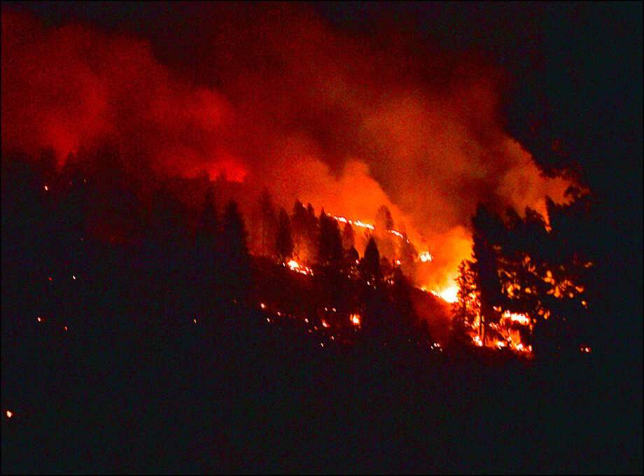 A consequence of climate change -- longer, more severe fire seasons. Here, a massive wildfire burns a hillside near Addy, Washington on Aug. 15, 2015. Several fires in Stevens County stretched state and local fire forces thin, driving some homeowners to battle the flames themselves. Photo: Tyler Tjomsland/Spokesman-Review/AP