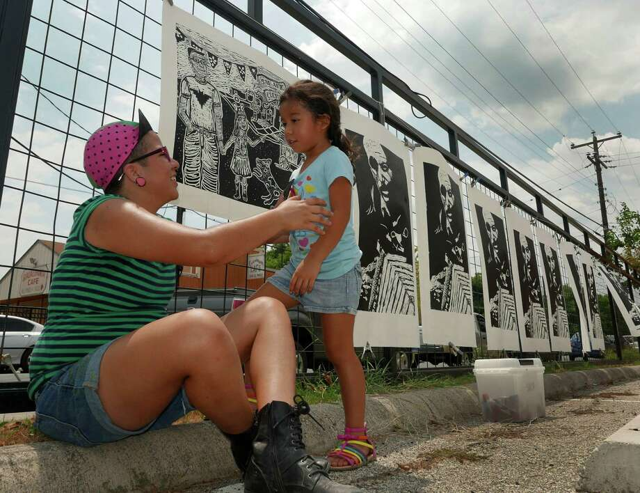 Artist Sabrina Alfaro greets daughter Kiley near the prints created by a steamroller over inked woodcuts. The art was the focus of the San Anto Cultural Arts Chupa- changa. Photo: Billy Calzada /San Antonio Express-News / San Antonio Express-News