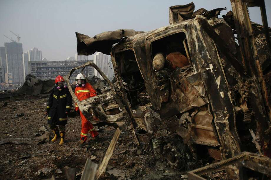 Firefighters walk past a damaged truck at the site of the explosions in Tianjin on August 15, 2015. Residents near the site of two giant explosions in the northern Chinese port city of Tianjin were being evacuated on August over fears of toxic contamination, state media said. CHINA OUT     AFP PHOTOSTR/AFP/Getty Images Photo: STR, Stringer / AFP / Getty Images / AFP