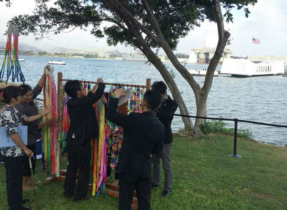People hang paper cranes folded for peace near a memorial to the sunken battleship USS Arizona before a ceremony marking the 70th anniversary of the end of World War II, Friday, Aug. 15, 2015, in Pearl Harbor, Hawaii. Mayors and city council members from Honolulu and Nagaoka, Japan, joined the U.S. Pacific Fleet commander to lay wreaths and unveil a new plaque. (AP Photo/Audrey McAvoy) Photo: Audrey McAvoy, STF / AP