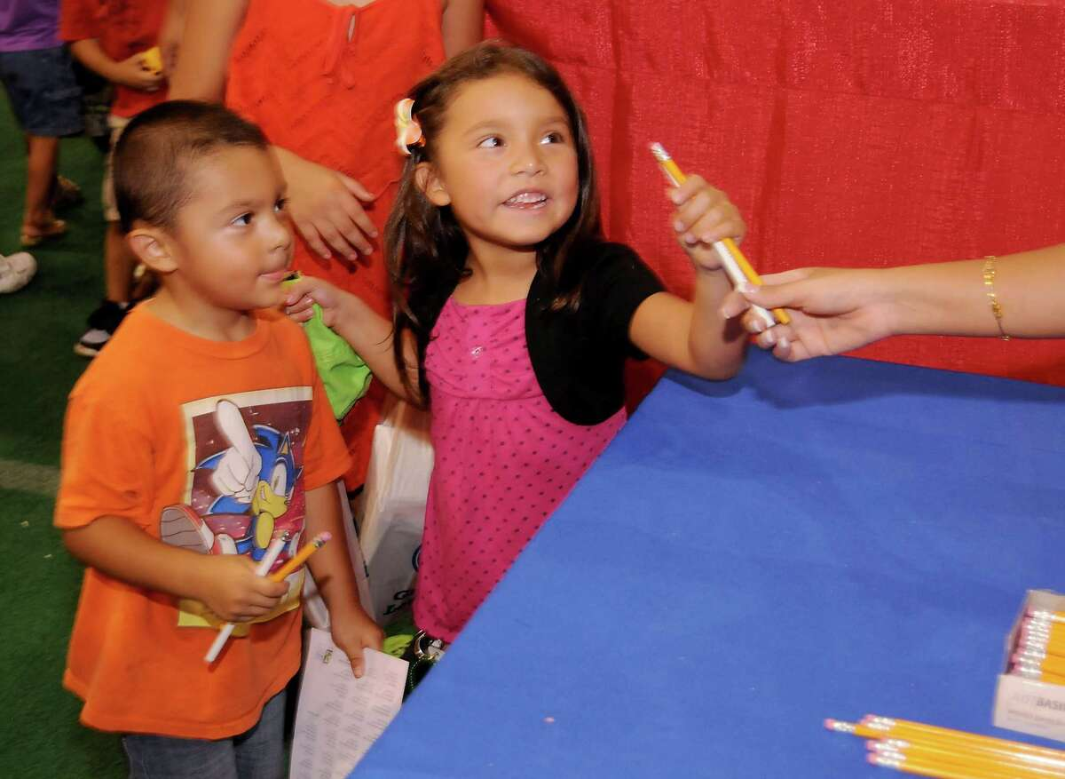 Ray and Selena Martinez receive pencils from the Department of Public Works booth at the Mayor's Back 2 School Fest at the University of Houston Saturday August 15, 2015.(Dave Rossman photo)
