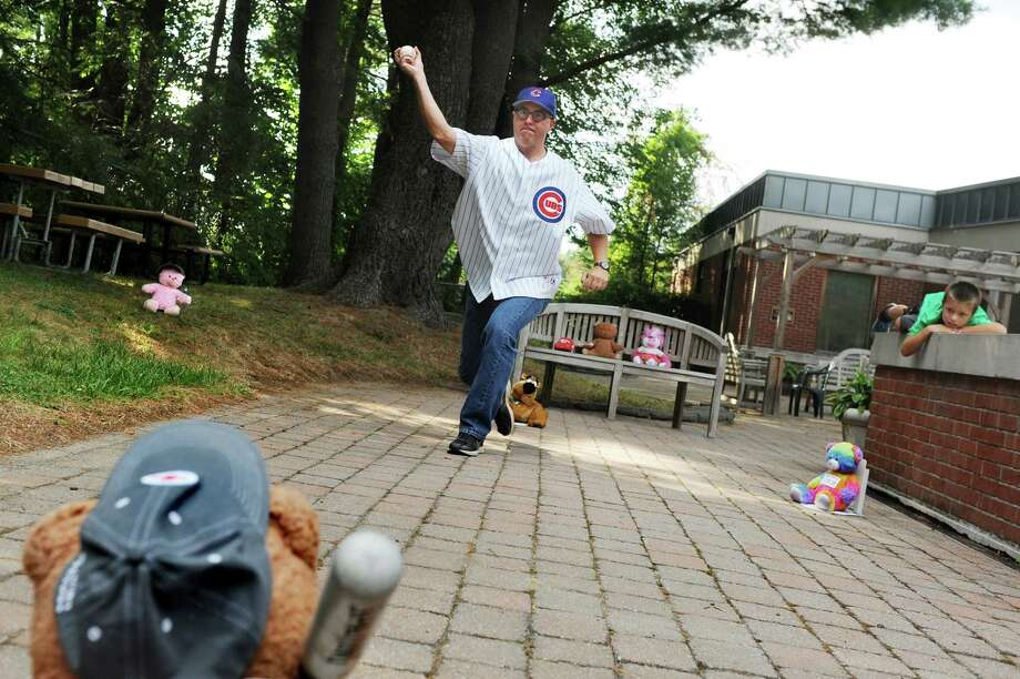 Library director Tim Wiles, center, throws a pitch to the teddy bear at bat as his son Ben Wiles, 8, right, watches on Friday, Aug. 14, 2015, at Guilderland Library in Guilderland, N.Y. Children dropped off their favorite stuffed animals for super adventures and a slumber party. Library staff and volunteers placed the toys in different situations to photograph and post on social media. (Cindy Schultz / Times Union) Photo: Cindy Schultz / 10032891A