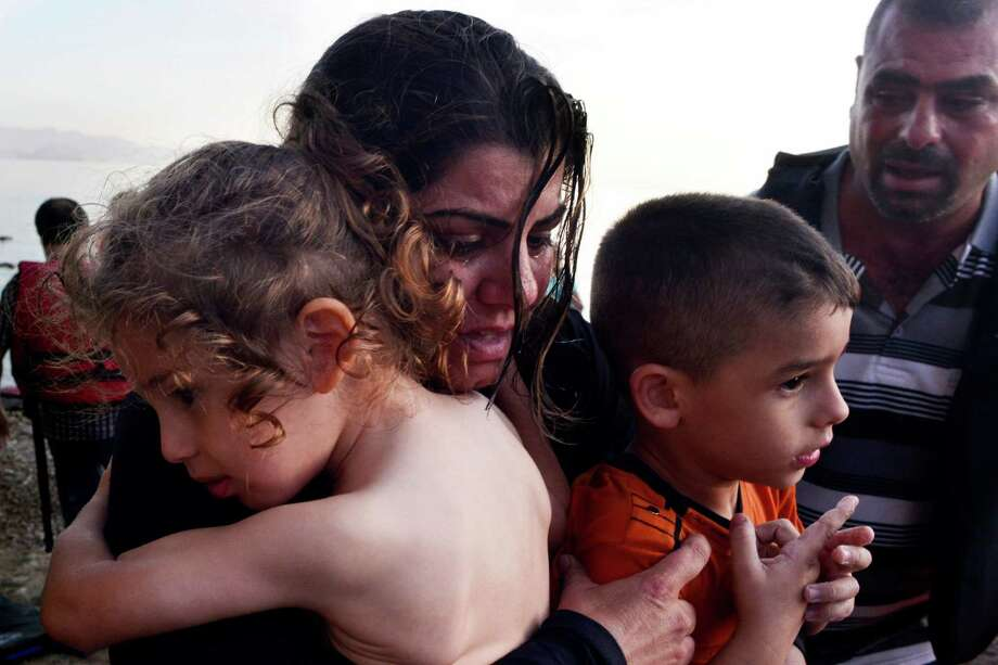 A Syrian family arrives at a beach on the Greek island of Kos after crossing part of the Aegean sea from Turkey to Greece in a dinghy. Other migrants have perished at sea. Photo: Milos Bicanski, Stringer / 2015 Getty Images