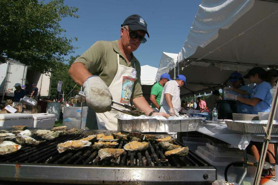 Tom Rossi puts oysters on the grill at the 41st Annual Milford Oyster Festival in downtown Milford, Conn., on Saturday Aug. 15, 2015. Some of the activities included the Gin Blossoms, which headlined the musical events at Fowler Field. National acts Fastball and The Rembrandts also performed. There were amusement rides, arts & crafts, a car and motorcycle show and the most variety of oysters from eight states. Photo: Christian Abraham, Hearst Connecticut Media / Connecticut Post
