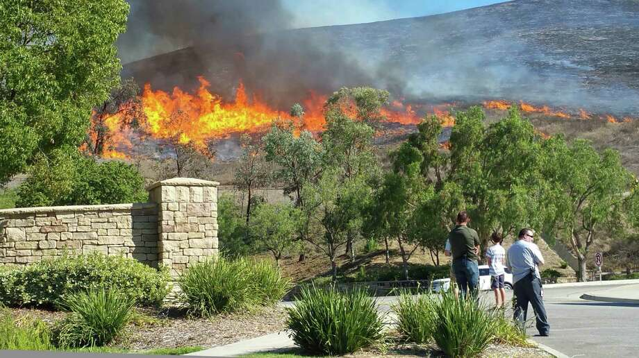 People watch a wildfire in the Wood Ranch area of Simi Valley, Calif., about 60 miles northwest of Los Angeles. No evacuations had been ordered in that area Friday afternoon. Photo: Joseph Garcia /Ventura County Star / Ventura County Star