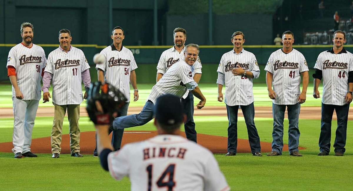 In an Astros managerial battery of sorts, Phil Garner unleashes the ceremonial first pitch to A.J. Hinch while members of Garner's 2005 team size up the toss Saturday night at Minute Maid Park.