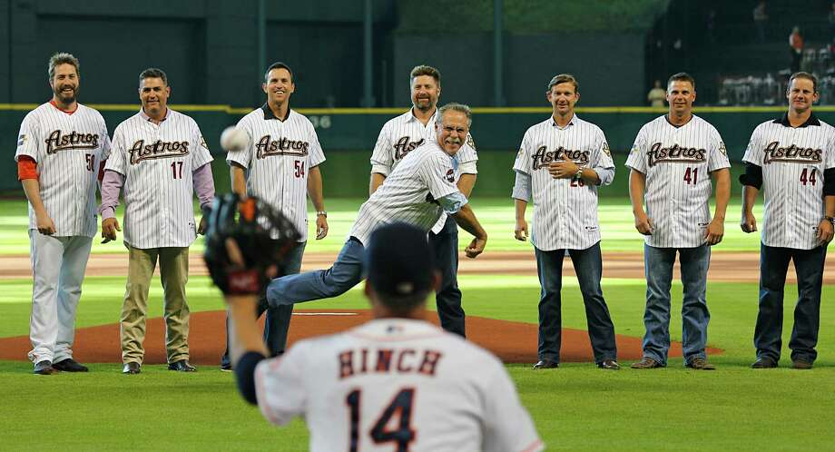 In an Astros managerial battery of sorts, Phil Garner unleashes the ceremonial first pitch to A.J. Hinch while members of Garner's 2005 team size up the toss Saturday night at Minute Maid Park. Photo: James Nielsen, Staff / © 2015  Houston Chronicle