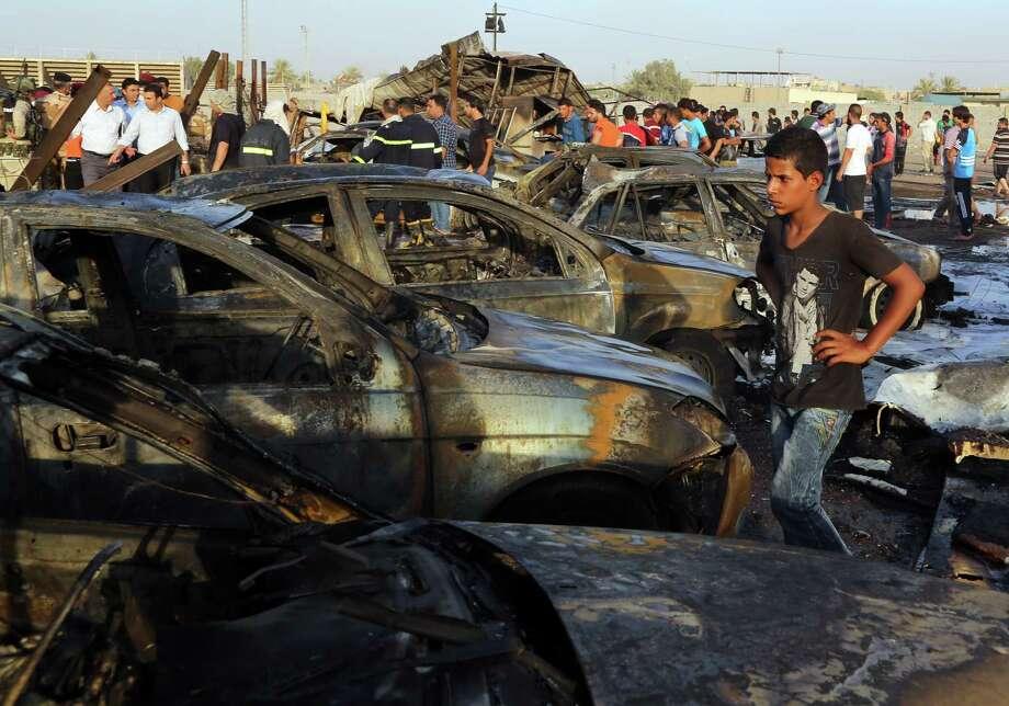 Civilians gather at the scene of a  bombing at a car dealership in the Habibiya neighbor-hood of Sadr City, Baghdad, Iraq, Saturday Photo: Karim Kadim, STF / AP