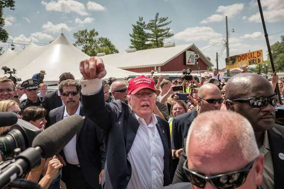 Donald Trump waves to the crowd at the Iowa State Fair. Trump took a walk through the fairgrounds with a mixture of media and curious onlookers trying to catch his every word. Illustrates IOWA-POLITICS (category a), by Philip Rucker and Jenna Johnson (c) 2015, The Washington Post. Moved Saturday, August 15, 2015.