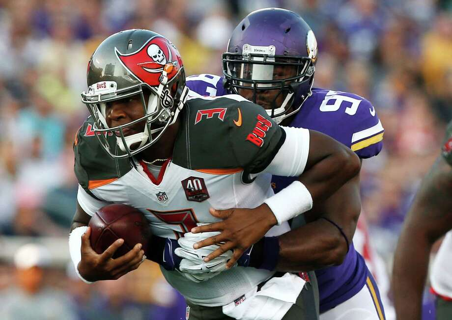 Welcome to the NFL, rookie. The Buccaneers' top draft pick, Jameis Winston, left, gets sacked by the Vikings' Everson Griffen on Saturday night. Photo: Jim Mone, STF / AP