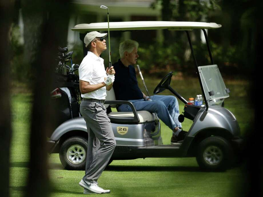 President Barack Obama, left, watches the flight of his ball as former President Bill Clinton, right, looks on while golfing Saturday, Aug. 15, 2015, at Farm Neck Golf Club, in Oak Bluffs, Mass., on the island of Martha's Vineyard. Photo: Steven Senne, Associated Press / AP