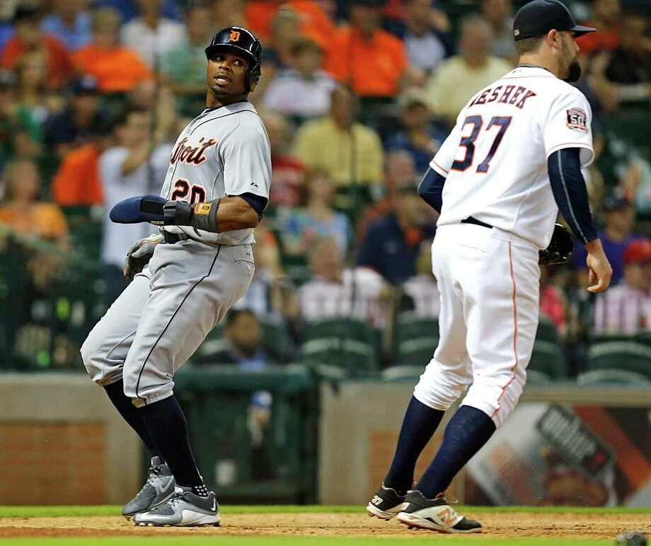 The Tigers' Rajai Davis, left, got the better of Astros reliever Pat Neshek, scoring one of Detroit's three 11th-inning runs. Photo: James Nielsen, Staff / © 2015  Houston Chronicle